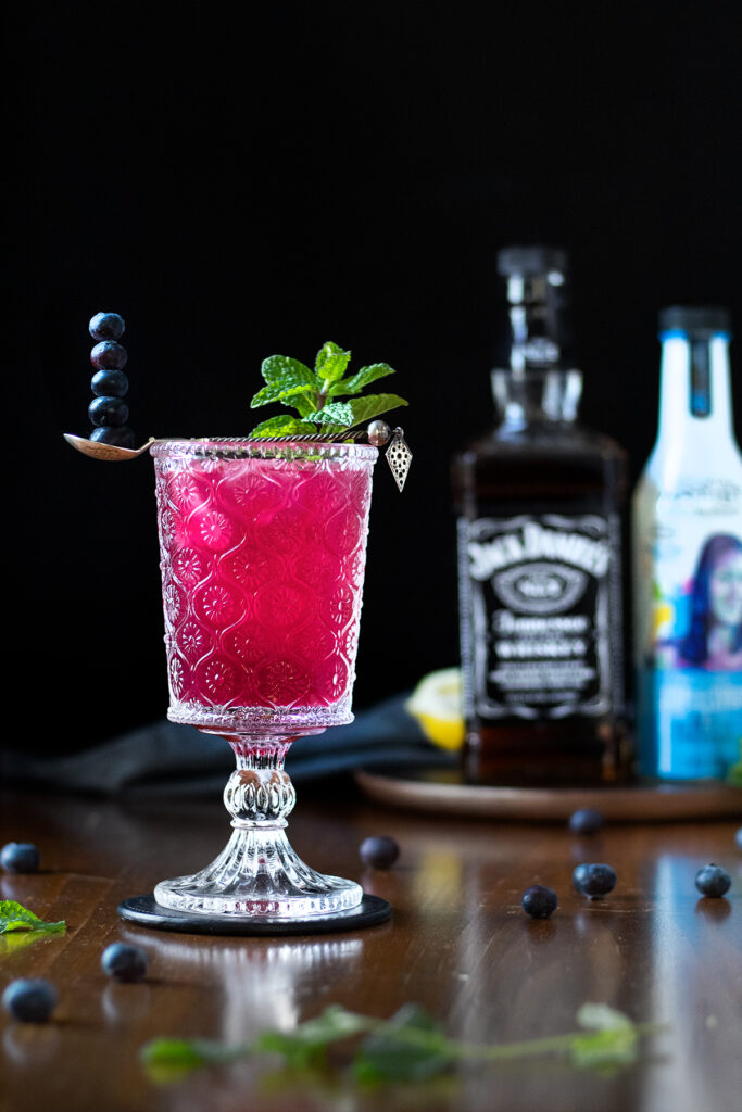 a bright pink cocktail with blueberries next to a bottle of Jack Daniels.