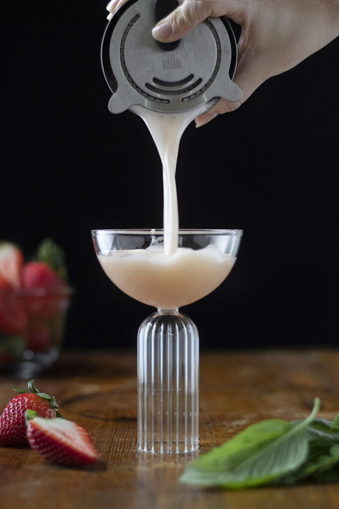 pouring-cocktail-from-shaker-into-coupe-glass-2