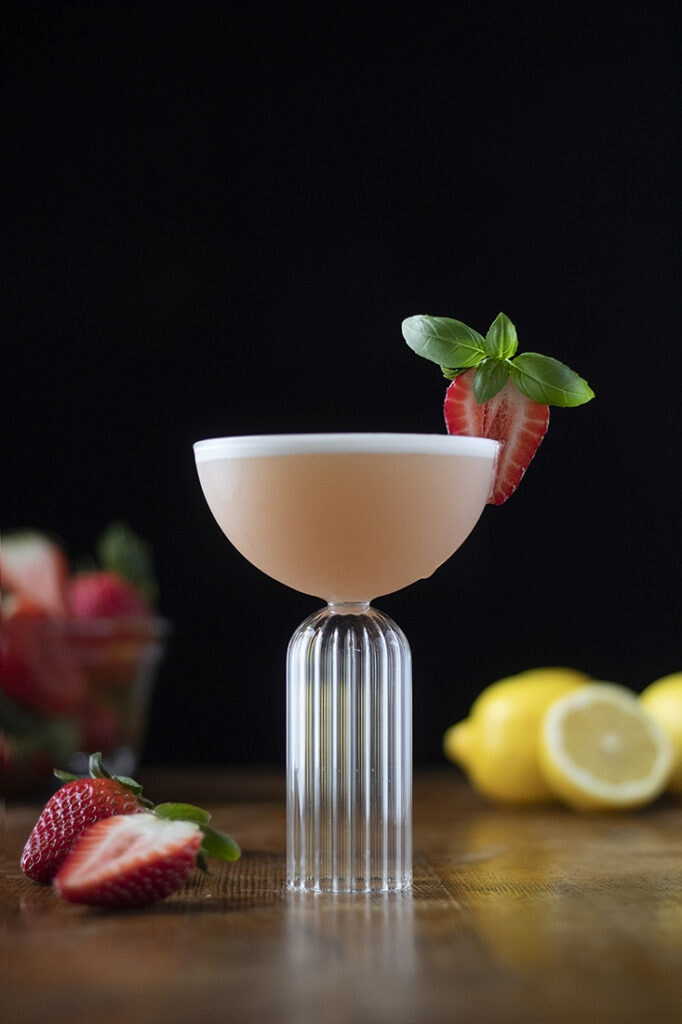 pink cocktail in a coupe glass garnished with a strawberry.