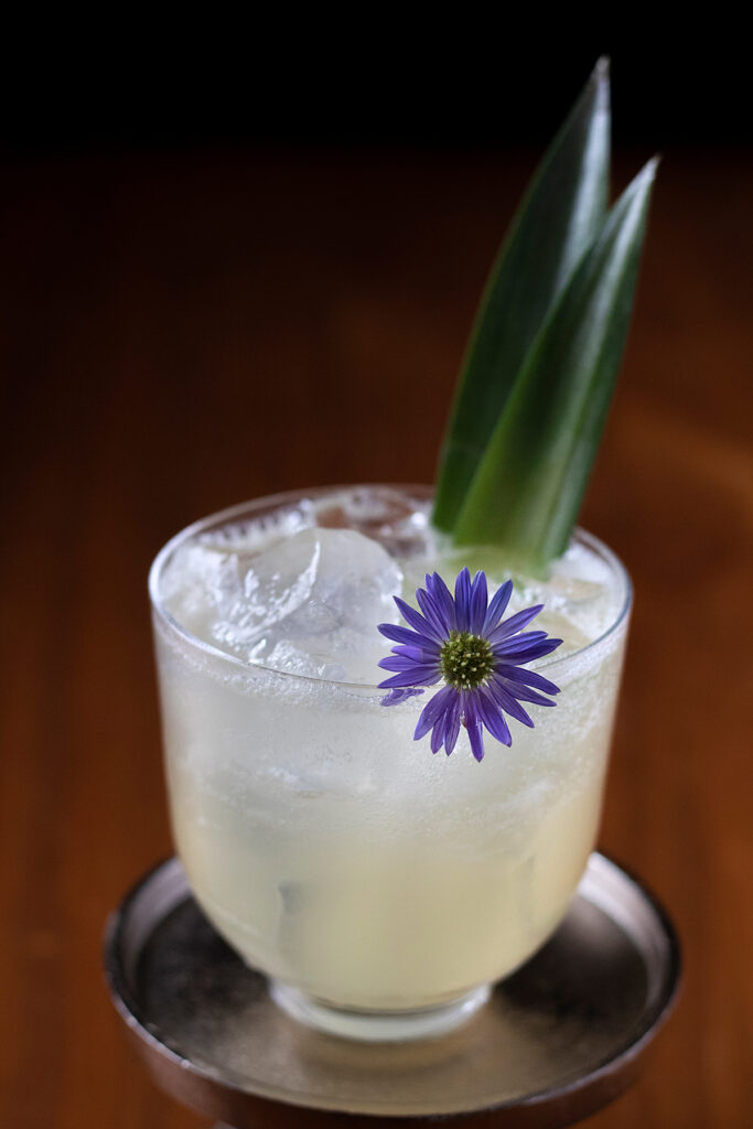 a pale yellow drink garnished with a purple flower and pineapple leaves.