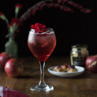 wine glass filled with a red bubbly cocktail with red flower.