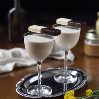 two creamy cocktails on a silver platter with wafer cookies.