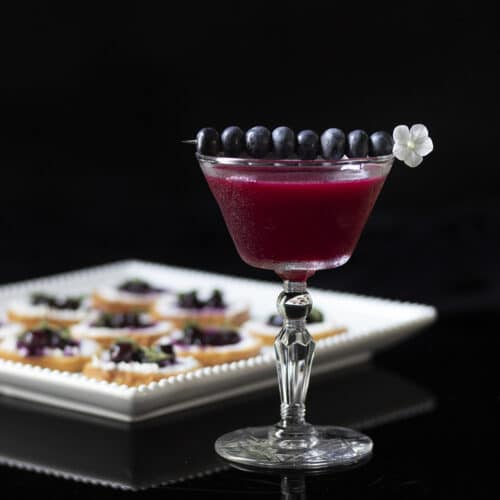 dark purple cocktail next to a platter of hors d'oeuvres