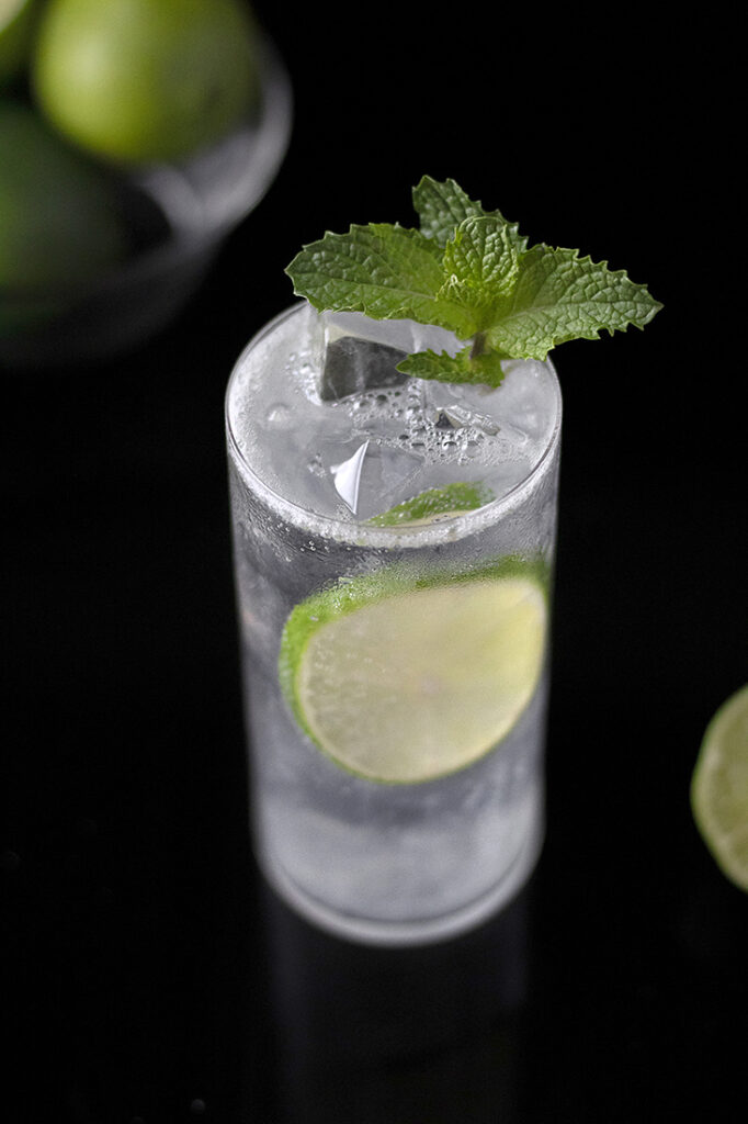 cocktail in highball glass with mint and lime