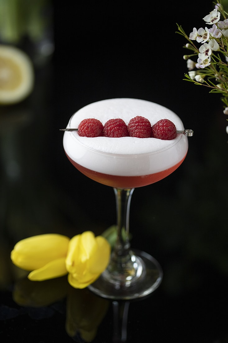 red cocktail with thick white foam on top and raspberries