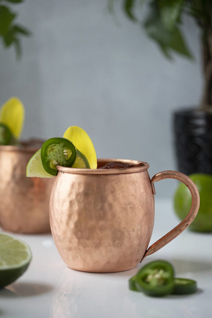 copper mule mugs garnished with jalapeno and flower petals