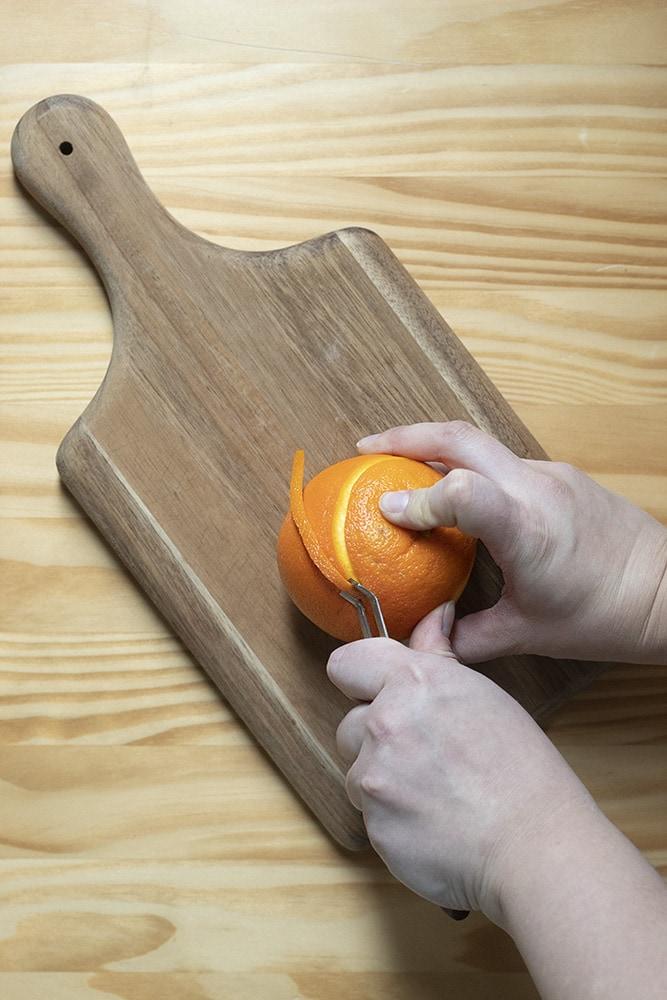 using a channel knife to peel a strip of orange peel