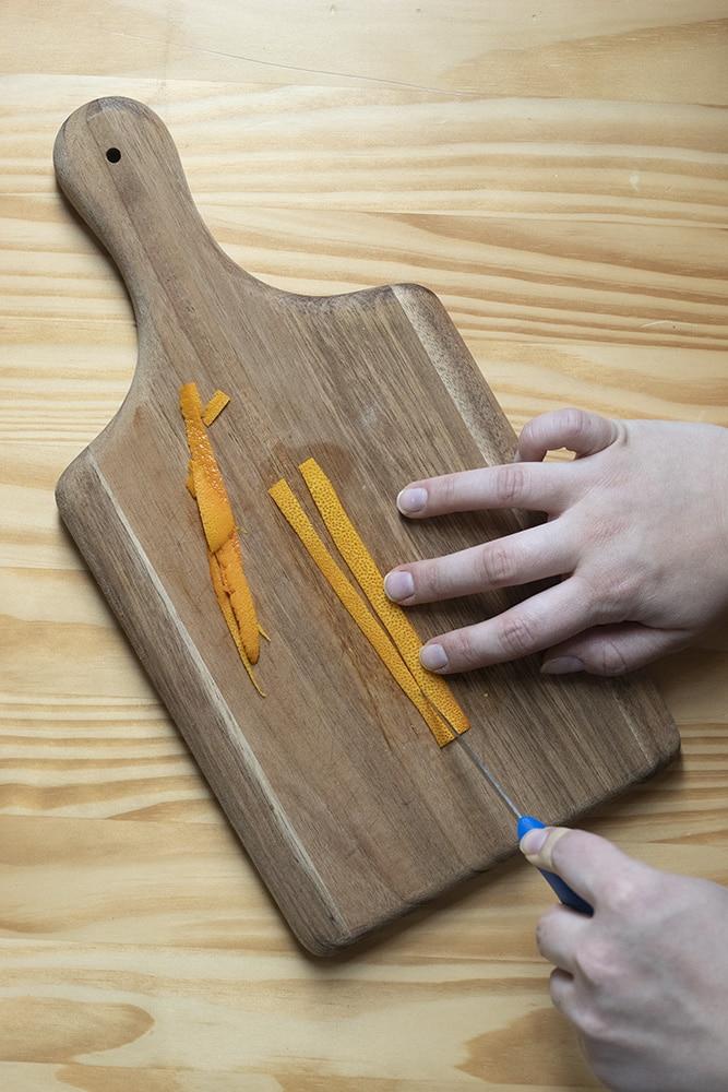 cutting an orange peel into thin strips