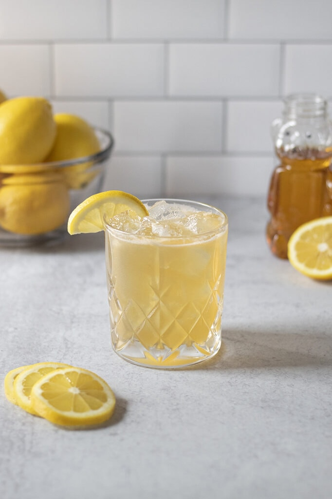 a yellow drink in a rocks glass next to lemons and honey.