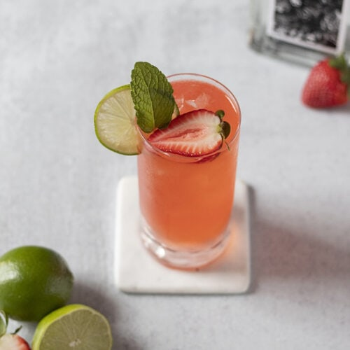 top down view of an orange colored highball cocktail with strawberries and lime