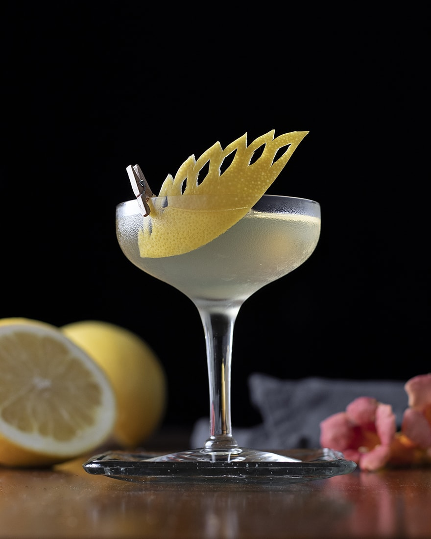 cocktail in coupe glass with carved citrus peel