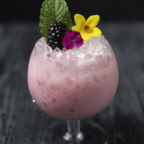 pink cocktail over crushed ice with edible flowers