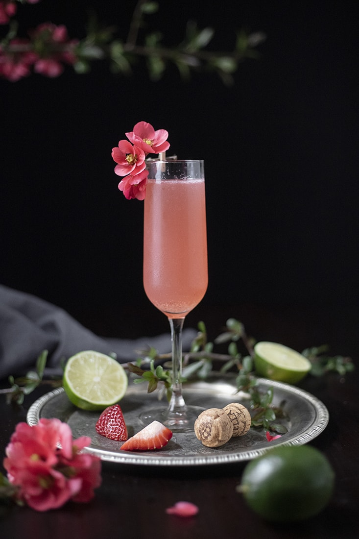 champagne flute with bright pink cocktail on a silver tray