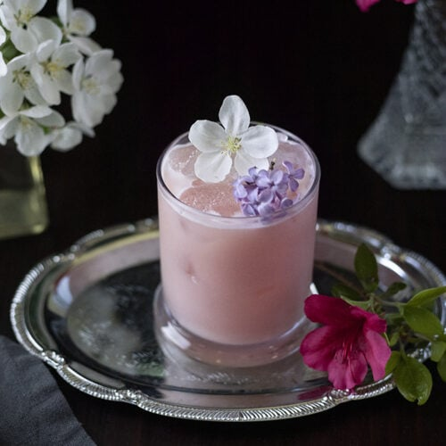 pink milky drink in a rocks glass surrounded by flowers