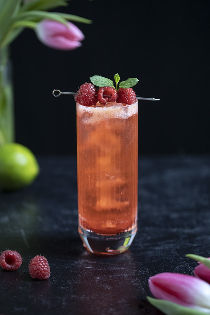 highball glass with red clear cocktail garnished with raspberries and mint
