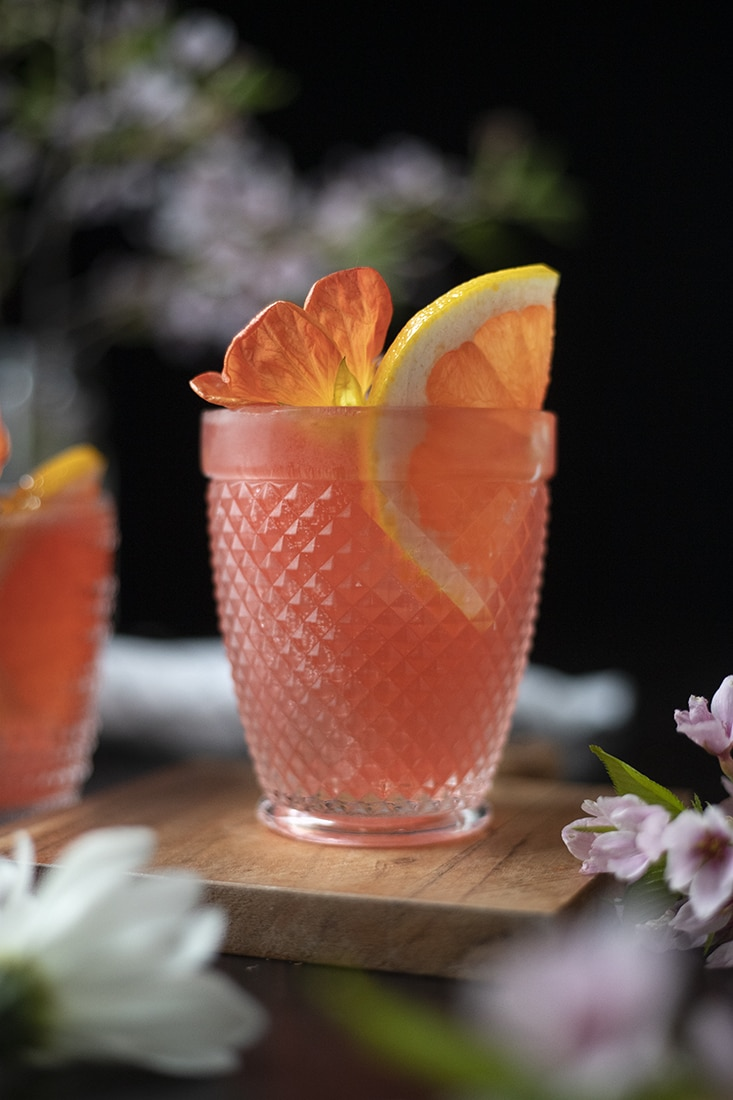 pink cocktail in a rocks glass with a slice of pink grapefruit