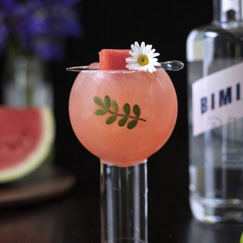 a pink cocktail in a balloon wine glass garnished with watermelon and a kinome leaf