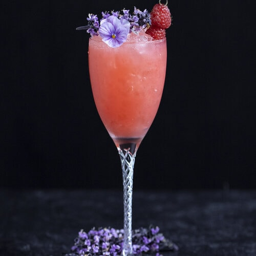 a long stemmed wine glass filled with a pink cocktail garnished with purple flowers