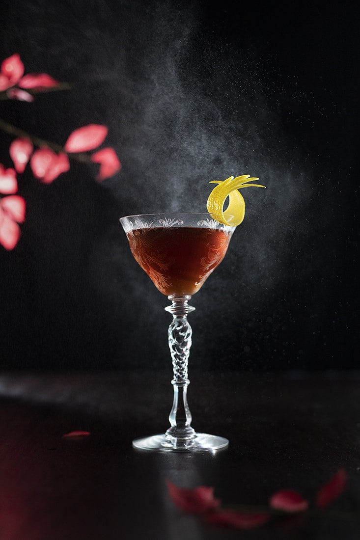 cocktail on black background with lemon peel
