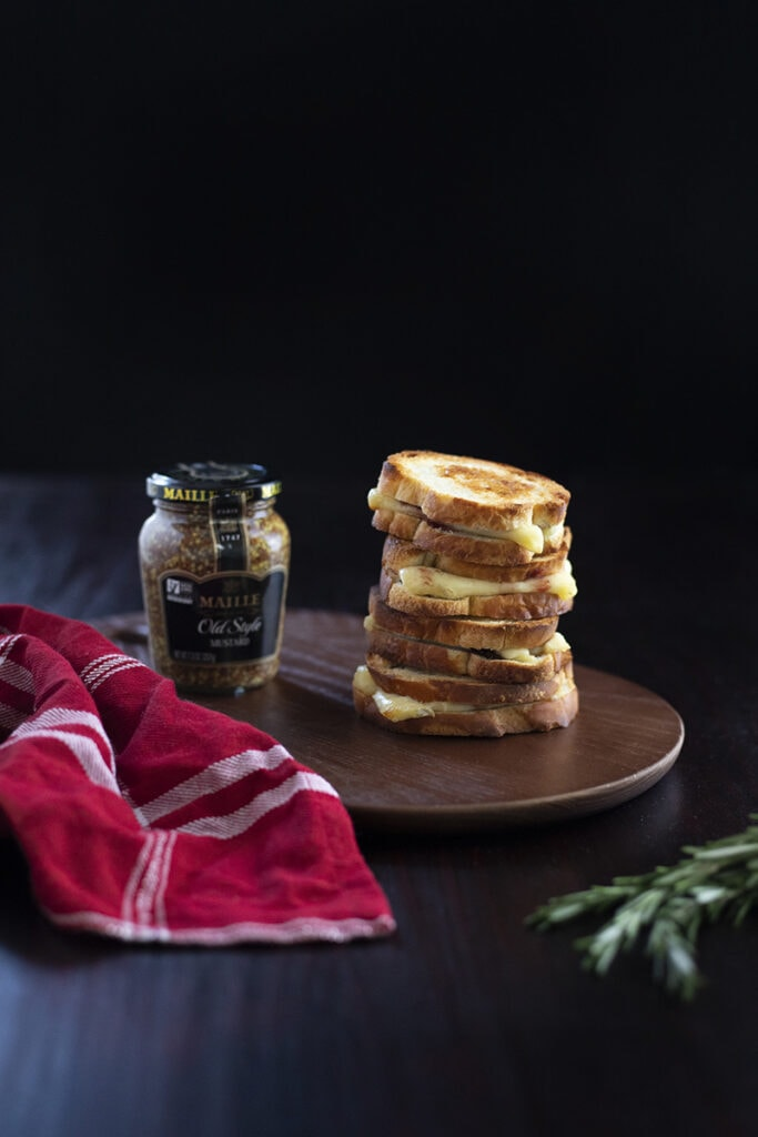 stack of miniature grilled cheese sandwiches on cutting board