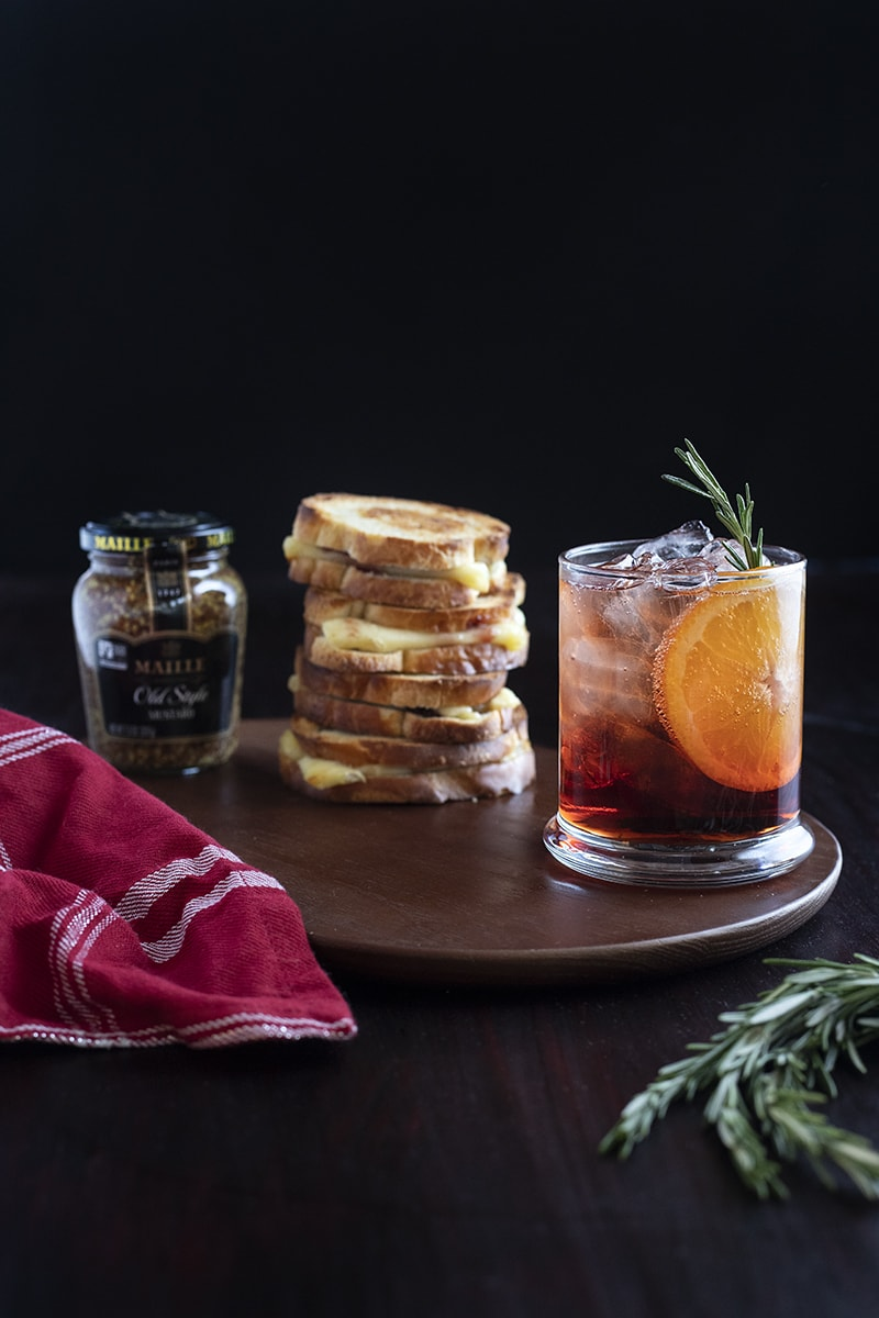 red cocktail on table with grilled cheese sandwich stack and jar of mustard