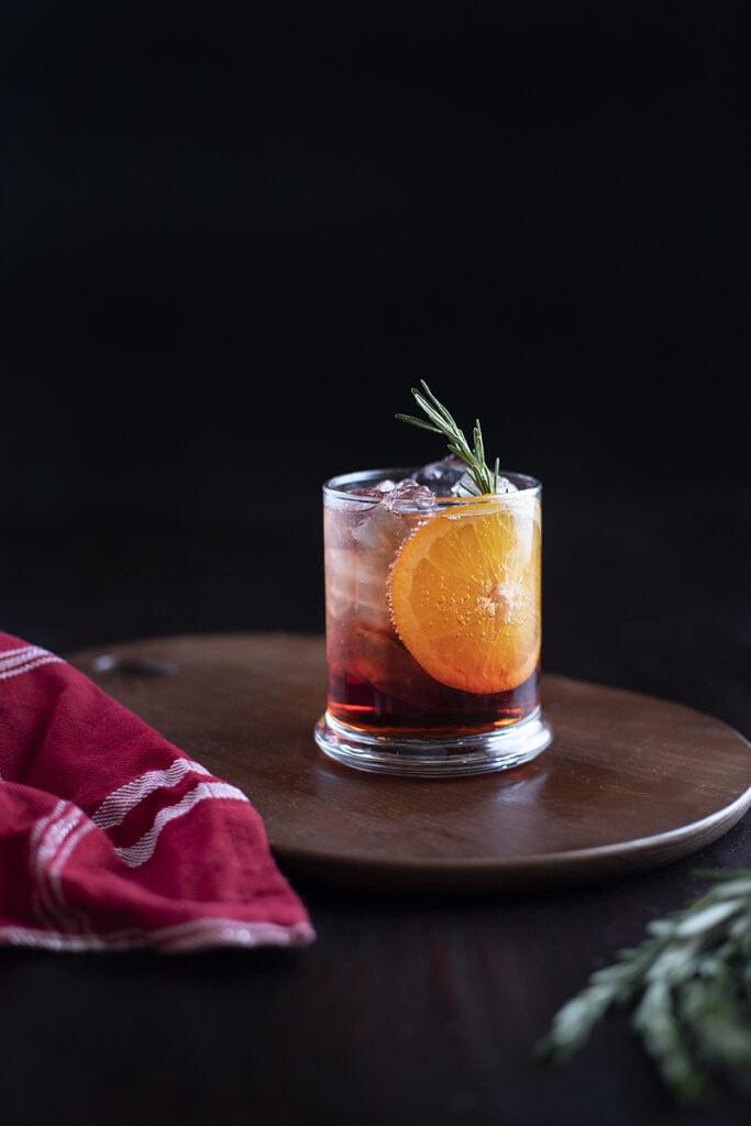 dark red cocktail with orange slice
