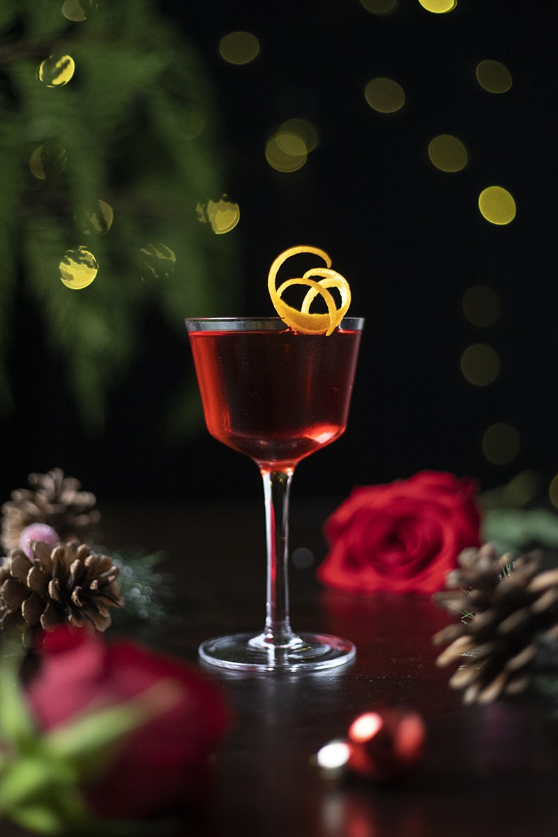 red cocktail in a nick and nora cocktail glass with an orange twist