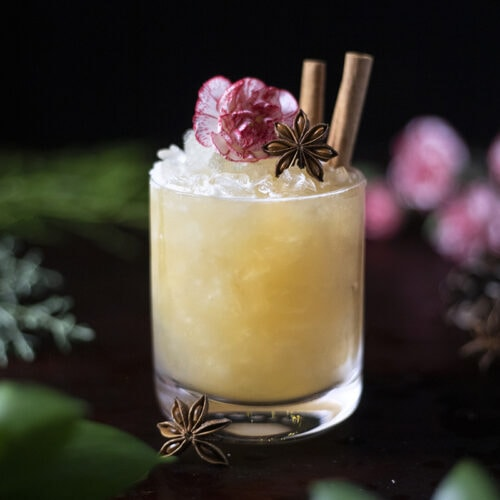 yellow cocktail in a rocks glass with crushed ice, star anise and cinnamon sticks