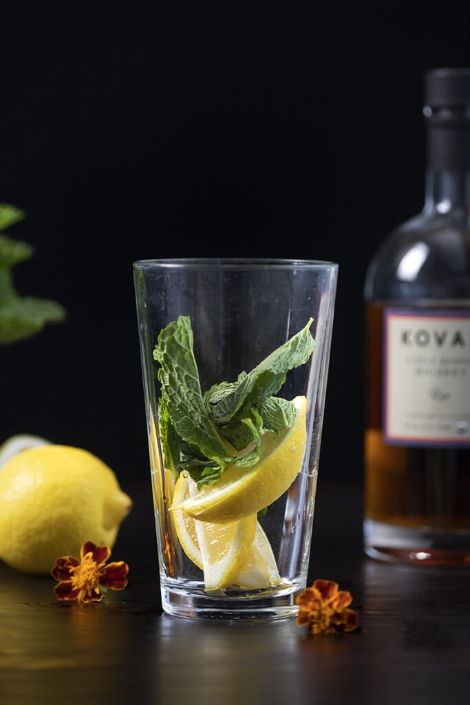 mint and lemon wedges in a pint glass
