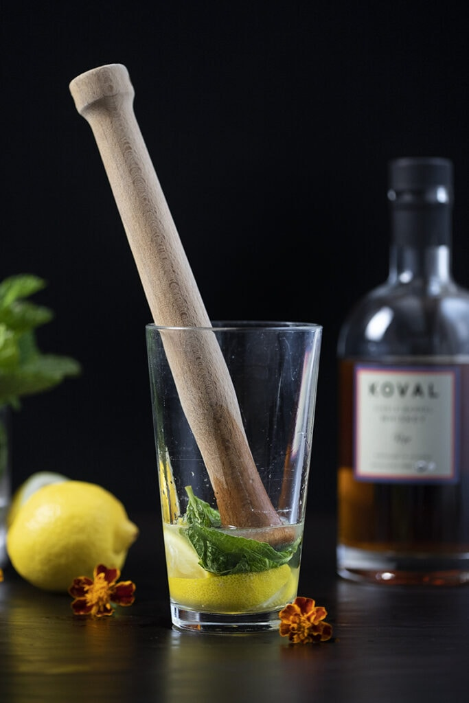 wooden muddler in a cocktail shaker with mint and lemon