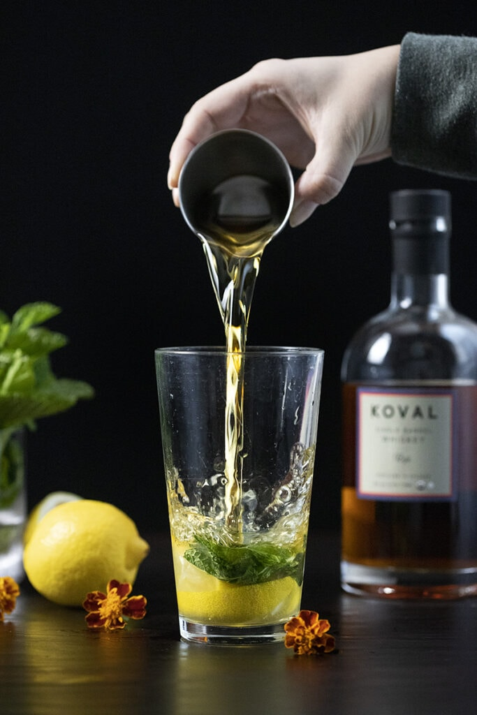 pouring whiskey into a cocktail shaker