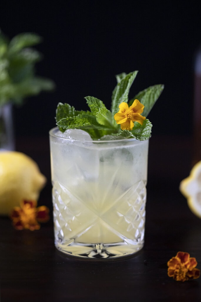 yellow cocktail in a rocks glass with mint and a yellow flower