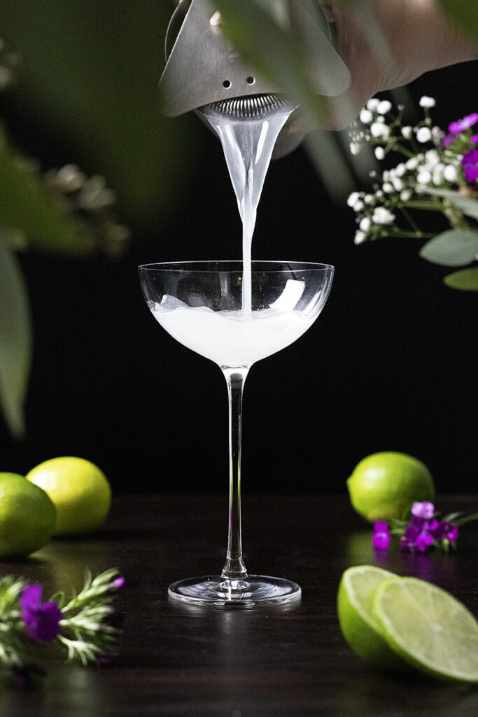 pouring a cocktail into a coupe glass