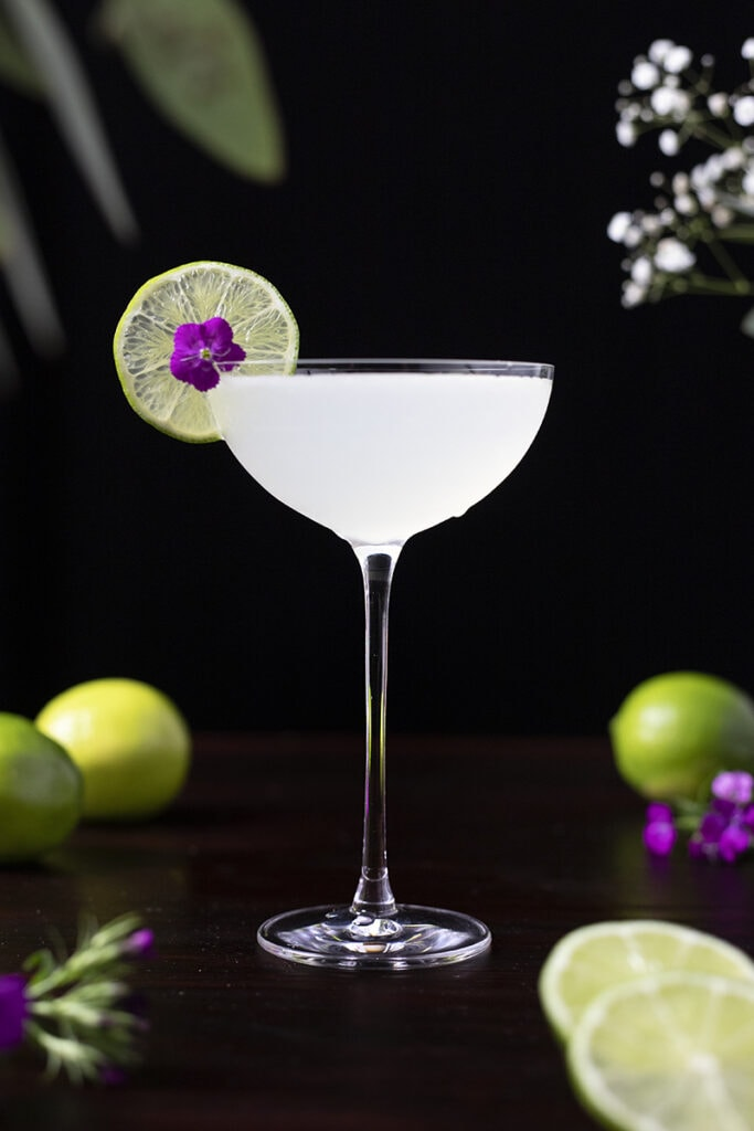 white cocktail in a stemmed glass garnished with a lime wheel and purple flower