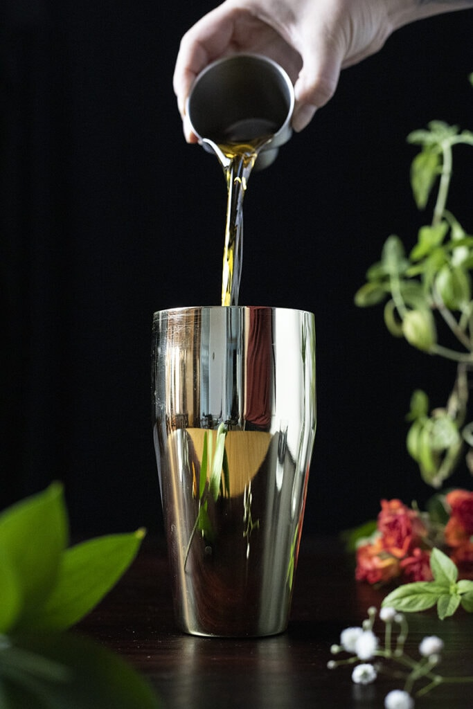 pouring whiskey into a gold cocktail shaker