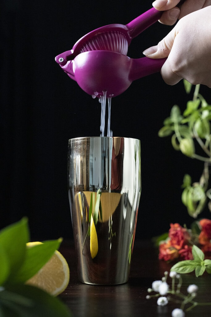 squeezing lemon juice into a gold cocktail shaker