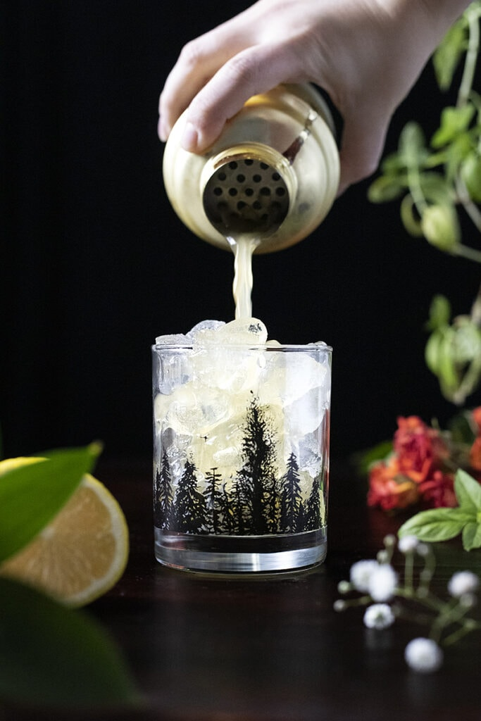 pouring a cocktail from a shaker into a rocks glass filled with ice