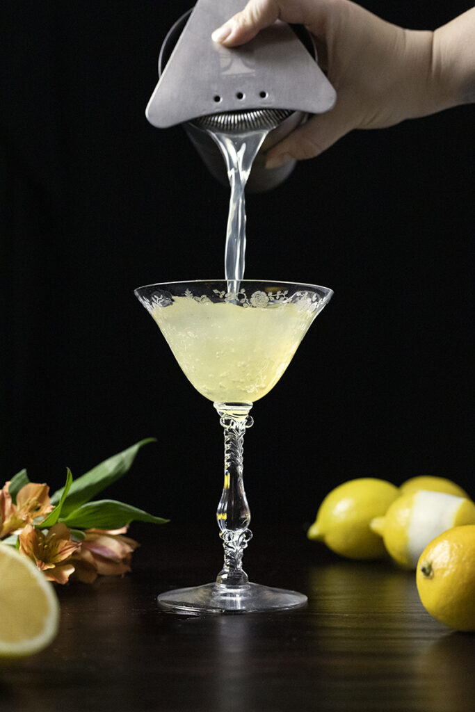 straining a cocktail into a vintage coupe glass
