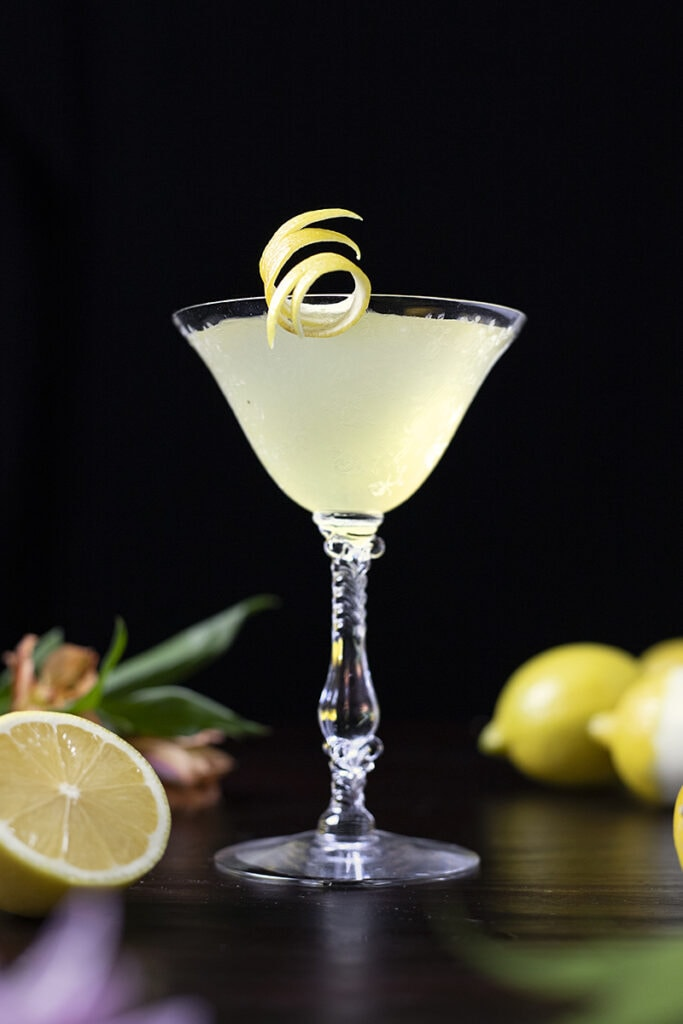 yellow cocktail in a vintage coupe glass wwith lemons