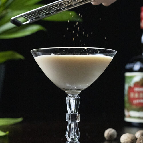 grating nutmeg over a creamy cocktail