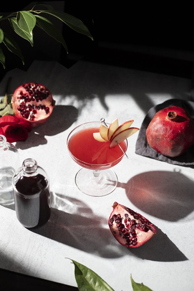 overhead view of a table with a bottle of grenadine, pomegranates, and a red cocktail