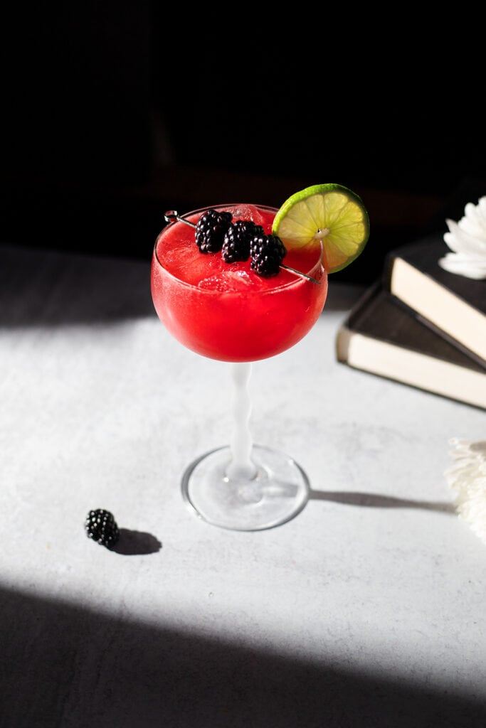 a bright red drink in a stemmed glass garnished with blackberries