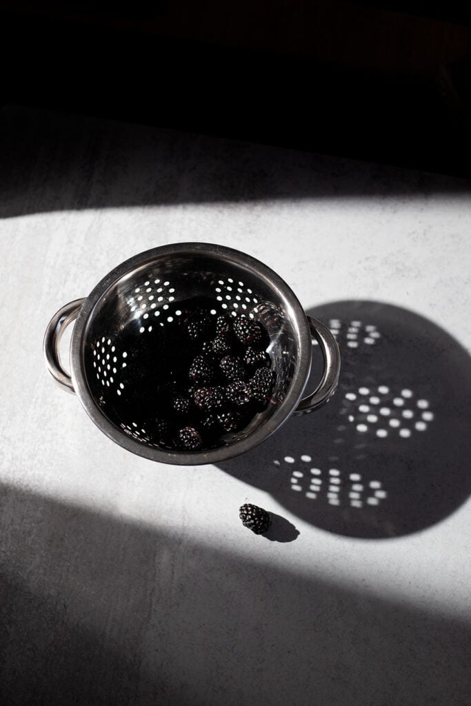 metal colander filled with blackberries