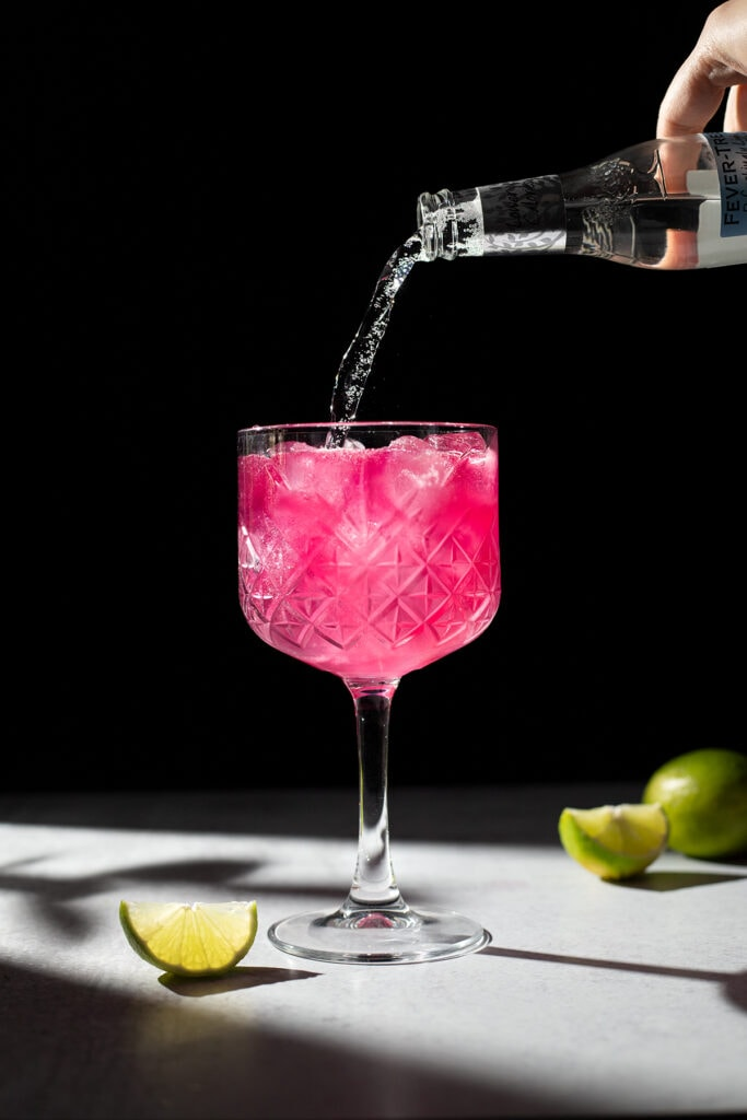 pouring tonic water into a pink drink