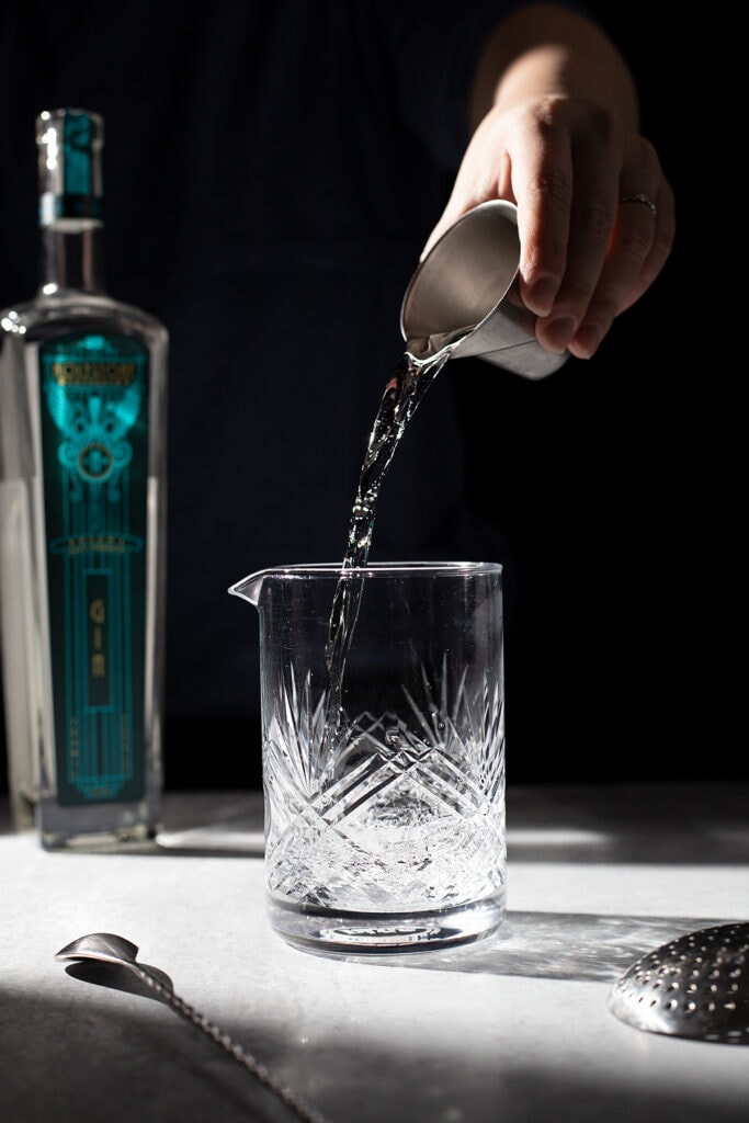 pouring gin from a jigger into a mixing glass.