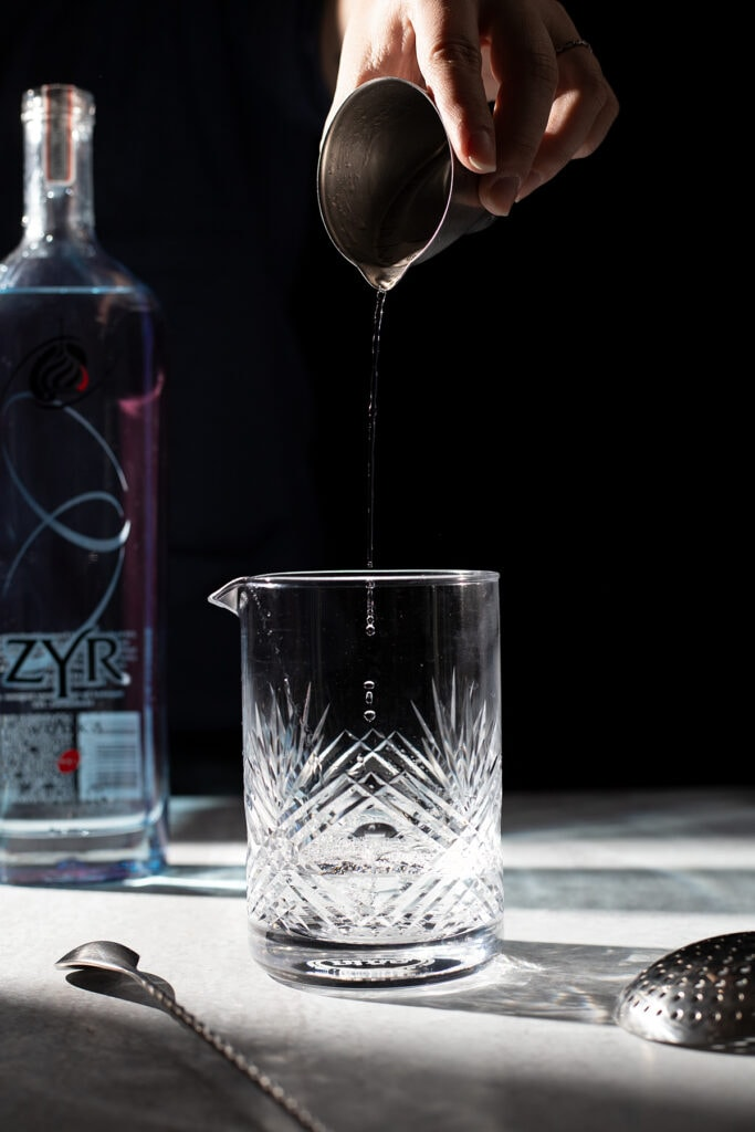 vodka droplets falling into a mixing glass.