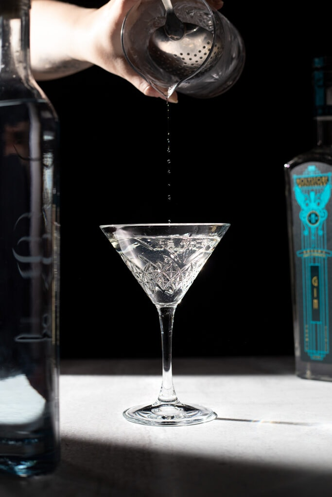 pouring the last drops of a cocktail from mixing glass to martini glass