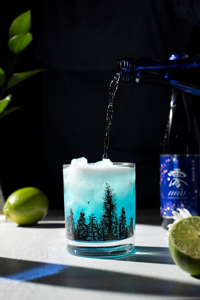 pouring sparkling sake into a blue drink over ice.