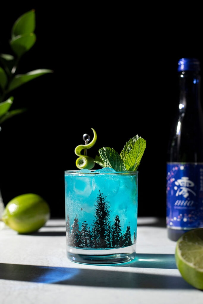 a blue drink in a rocks glass next to a bottle of sparkling sake and limes.