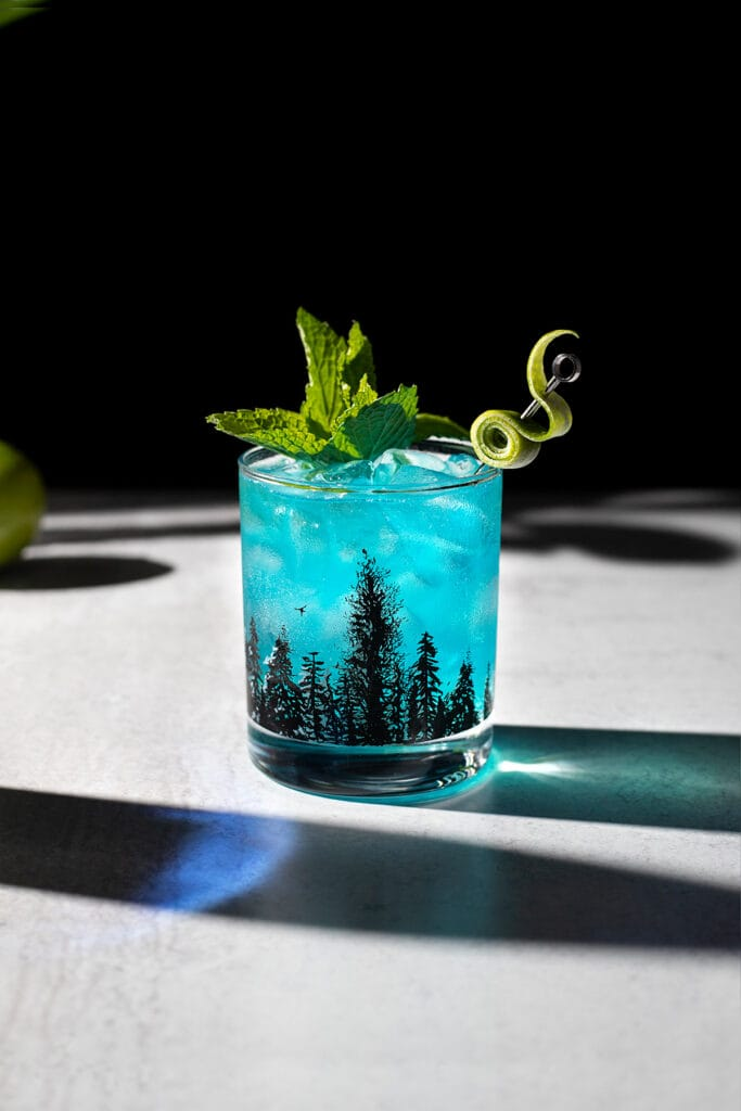 a blue drink with a sprig of mint and a fancy lime twist.